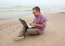 Gamal mansammanträde med en bärbar dator Arkivbilder