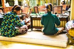 Gamala män som bär den traditionella likformign som spelar med gamla och forntida musikinstrument royaltyfria foton