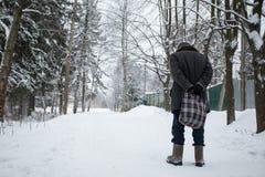 Gamala mannen går med en påse i vintern på vägen arkivbild