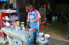 Gamala mannen gjorde frukosten och kaffe thai stil i Phrae Arkivfoton