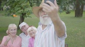 Gamala mannen i en hatt och ett grått skägg gör en selfie mot bakgrunden av hans vänner som sitter på en bänk i, parkerar Tv? arkivfilmer