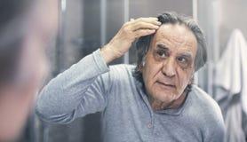 Gamala mannen kontrollerar hårförlust royaltyfri foto