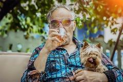 Gamala mannen med en hund tycker om liv arkivfoto