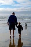 Gamala mannen och barnpojken undersöker stranden Arkivfoton