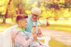 Gamala mannen och pojken som äter glass på sommar, parkerar Arkivfoto