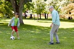 Gamala mannen och pojken som spelar fotboll på sommar, parkerar Arkivbild