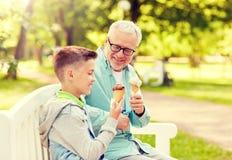 Gamala mannen och pojken som ?ter glass p? sommar, parkerar arkivfoto