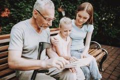 Gamala mannen och unga flickan sitter på bänk Bok på bänk arkivfoton