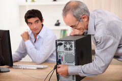 Gamala mannen pluggar en dator Royaltyfria Foton