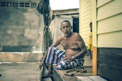 Gamala mannen reparerade hans träsäng Arkivfoto