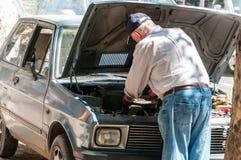 Gamala mannen reparerar hans brutna Yugo bil på gatan Royaltyfria Bilder