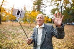 Gamala mannen rymmer en mobiltelefon med en monopod och vinkar hans hand arkivbilder