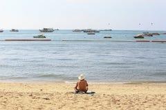 Gamala mannen solbadar på stranden, Pattaya Thailand, som bakgrund Arkivbild