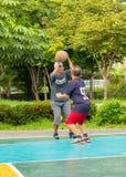Gamala mannen som är lycklig med övning att spela basket på BangYai, parkerar arkivfoton