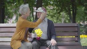 Gamala mannen som kysser hans kvinna med blommor p? banchen i en v?r, parkerar arkivfilmer