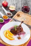 Gamba arrostita dell'anatra sul vassoio con vetro di vino rosso Immagini Stock