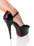 Gamba con le scarpe rosse e nere del feticcio dei pizzi sulla parte posteriore di bianco Fotografie Stock Libere da Diritti