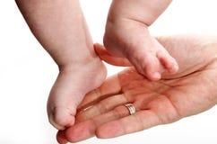 Gamba del bambino in mano del padre Immagini Stock