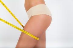 Gamba della donna circondata da un nastro di misurazione Fotografia Stock