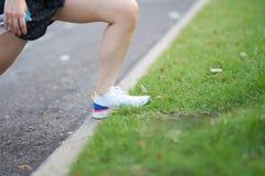 Gamba della donna sull'allungamento del muscolo prima dell'esercizio nella mattina Fotografia Stock
