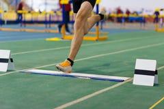 Gamba di atterraggio dello sportivo sul difetto prima del salto fotografie stock