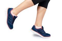 Gamba femminile adatta in scarpa di sport isolata su fondo bianco fotografia stock