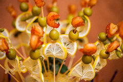 Gambas asadas a la parrilla en un pincho con las aceitunas verdes y el limón Fotos de archivo