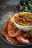 Gambas asadas a la parrilla fritas con los tallarines de arroz, la salsa y la lechuga, fondo oscuro imagen de archivo