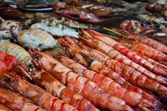 Gambas asadas a la parrilla y otros mariscos exhibidos en mercado de la noche Foto de archivo