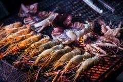 Gambas y calamar asados a la parrilla del rey en el fuego del Bbq Comida tailandesa de la calle en Chiang Mai Old City Night Mark imagen de archivo