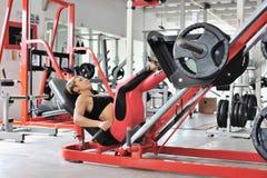 Gambe adatte di addestramento della donna su un simulatore della gamba alla palestra Immagini Stock