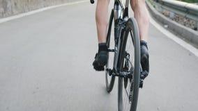 Gambe adatte scarne del ciclista con i forti muscoli che pedaling in salita dalla sella Addestramento di riciclaggio in salita Co video d archivio