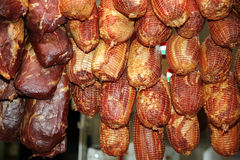 Gambe affumicate d'attaccatura della carne di maiale nel commercio al dettaglio Fotografia Stock