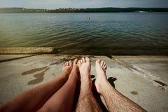 Gambe alla moda felici delle coppie, prendenti il sole alla spiaggia, vacat di estate Immagine Stock Libera da Diritti