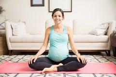 Gambe attraversate seduta sorridenti della donna incinta sulla stuoia di forma fisica immagini stock