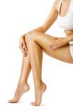 Gambe bellezza, Sitting di modello su bianco, pelle del corpo della donna della gamba di tocco fotografia stock