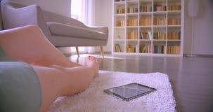 Gambe caucasiche femminili che si muovono sul tappeto beige con la compressa che si trova vicino nel salone sul fondo degli scaff archivi video