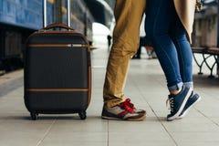 Gambe che amano abbracciare felice delle coppie nella stazione ferroviaria di un paese dopo l'arrivo in autunno con una luce sola Immagine Stock