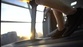Gambe che camminano sulla pedana mobile, addestramento dello sportivo di tramonto dopo il lavoro, distensione della tensione stock footage