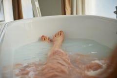 Gambe che riposano nella vasca di una persona Bagno di Cleopatra con latte Bellezza e rilassamento fotografie stock libere da diritti
