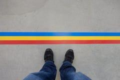 Gambe con i jeans e le scarpe da tennis ad una linea Fotografie Stock Libere da Diritti