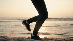 Gambe correnti della donna che pareggiano al tramonto alla spiaggia della costa di mare con il chiarore della lente di Sun video d archivio