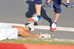 Gambe danneggiate del corridore maratona Immagini Stock