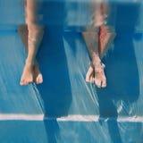 Gambe degli adulti subacquee nella piscina fotografia stock libera da diritti