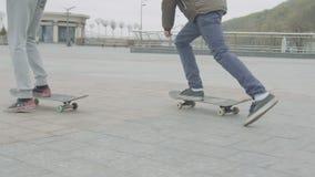 Gambe degli amici teenager che pattinano sul quadrato di città archivi video