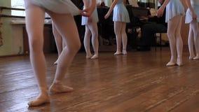 Gambe dei balerinas che fanno gli esercizi durante la lezione di balletto nell'aula di balletto stock footage