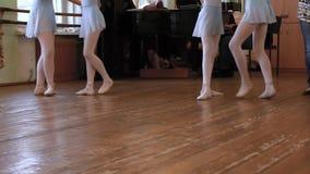 Gambe dei balerinas che fanno gli esercizi nelle paia durante la lezione di balletto stock footage