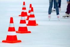 Gambe dei pattinatori di ghiaccio e coni a strisce bianchi rossi Fotografia Stock Libera da Diritti