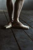Gambe del ballerino di balletto nei pointes che stanno sul pavimento nero Fotografie Stock Libere da Diritti