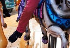 Gambe del bambino che pendono dal cavallo del carrousell fotografia stock libera da diritti